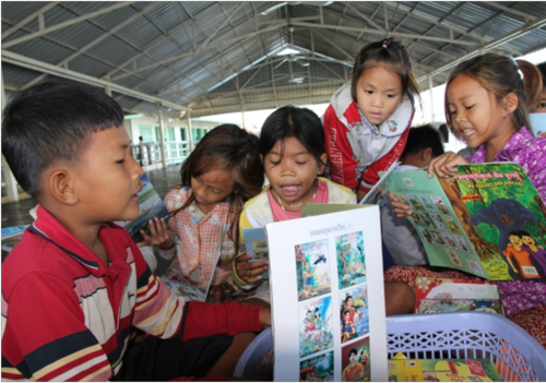 Children reading in the outdoor area.